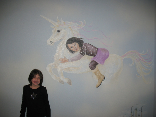 Gracie standing next to herself on a unicorn in the sky!